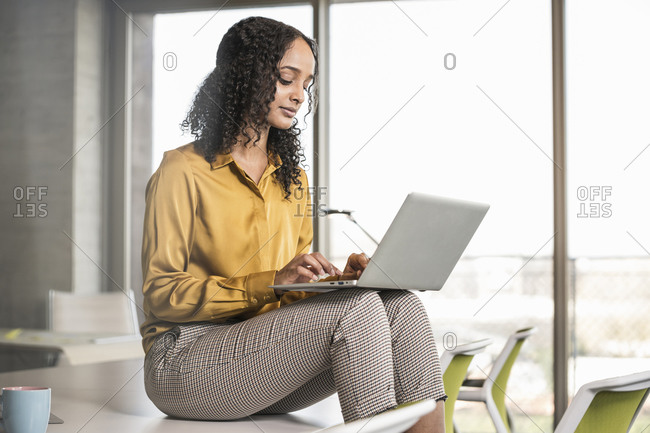 Young businesswoman sitting on desk in office using laptop