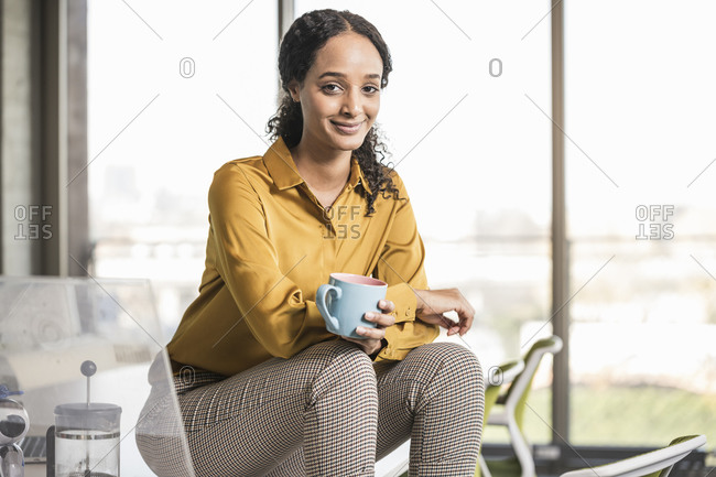 Portrait of smiling young businesswoman sitting on desk in office having a coffee break
