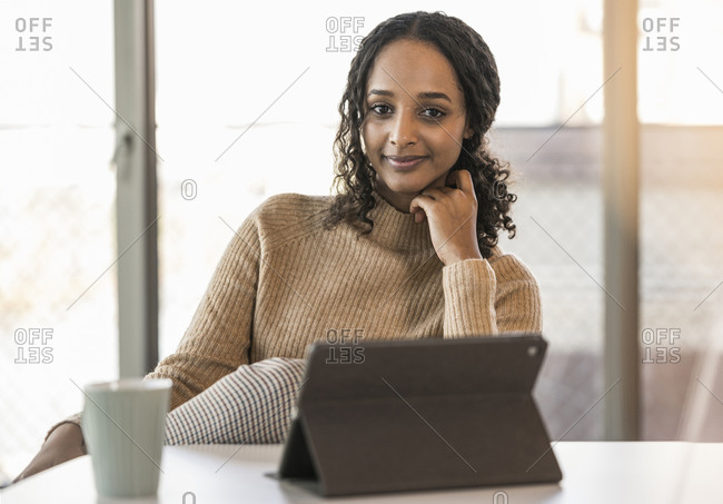 Portrait of smiling young businesswoman sitting at desk in office with tablet