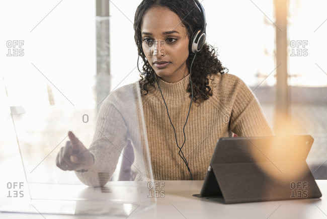Young businesswoman sitting at desk in office using transparent screen