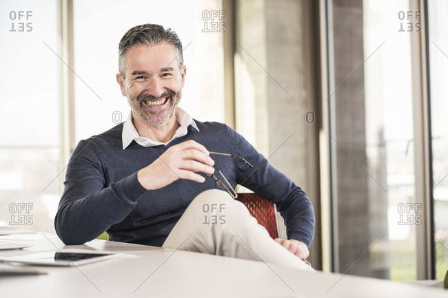 Portrait of a happy mature businessman sitting at desk in office