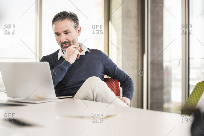 Mature businessman sitting at desk in office using laptop