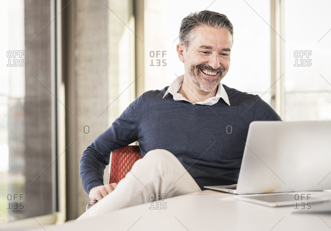 Smiling mature businessman sitting at desk in office using laptop