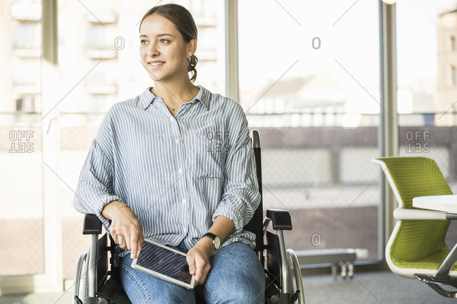 Young businesswoman with tablet sitting in wheelchair in office