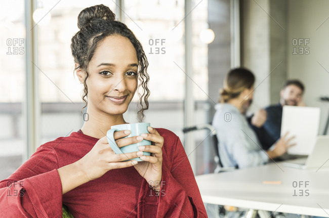 Portrait of smiling young businesswoman having a coffee break during a meeting in office