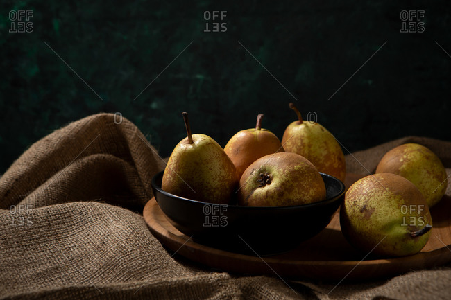 Whole pears in a bowl on wooden platter