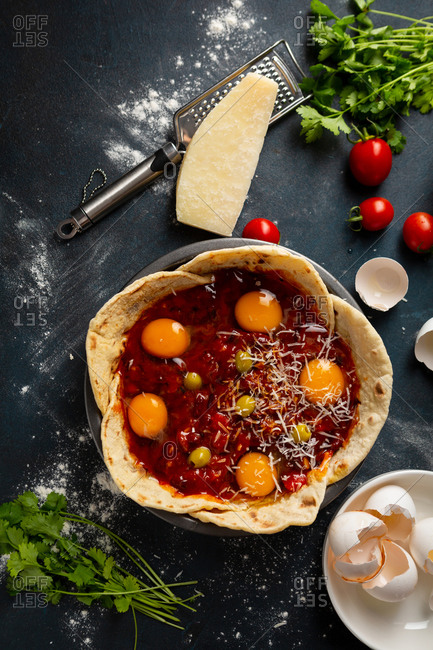 Breakfast shakshuka with tacos are being preparing on dark surface