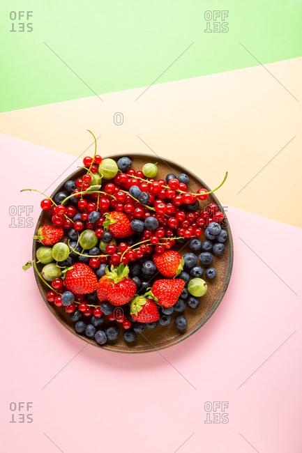 Overhead view of berries on tray on color paper background