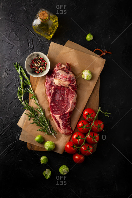 Raw beef steak. Rosemary, tomatoes