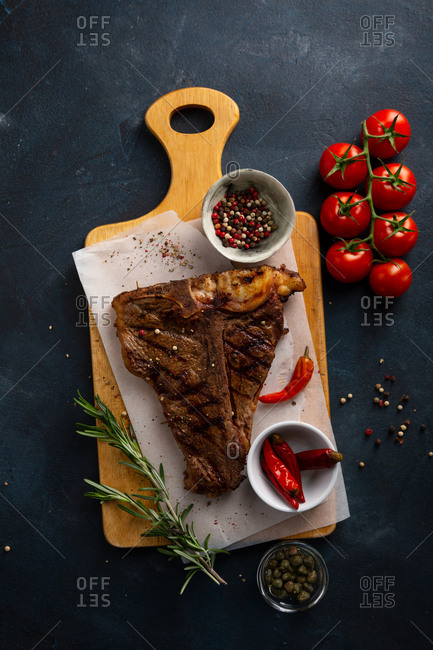 Cooked beef steak with rosemary on cutting board