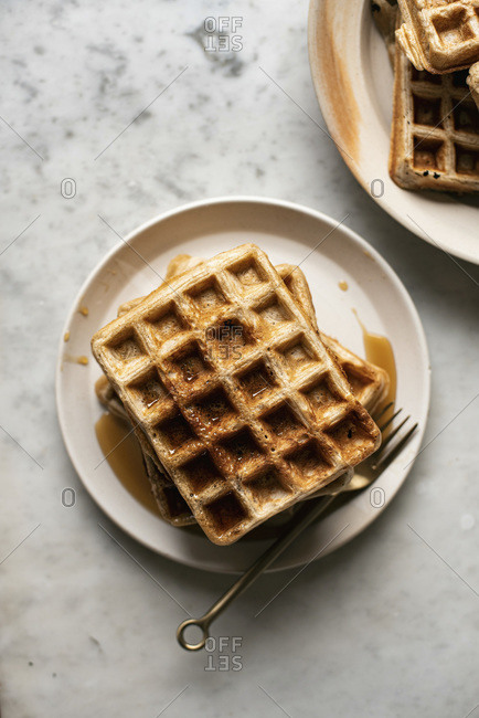 Square Waffles piled on a plate, top view