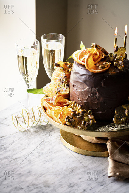 An Epic Gluten-free Chocolate Cake with ricotta cheese filling, chocolate frosting, chocolate glaze, orange slices and pistachio praline served with champagne.