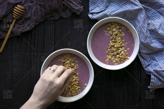 A hand sprinkling granola over smoothie bowl.