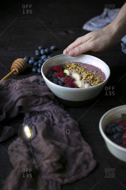 A hand holding a smoothie bowl.