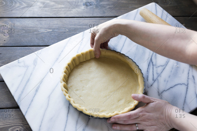 Step-by-step photo for rolling tart dough into a tart pan.