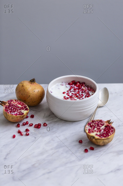 Pomegranate seeds and yoghurt in a white ceramic bowl on a marble table