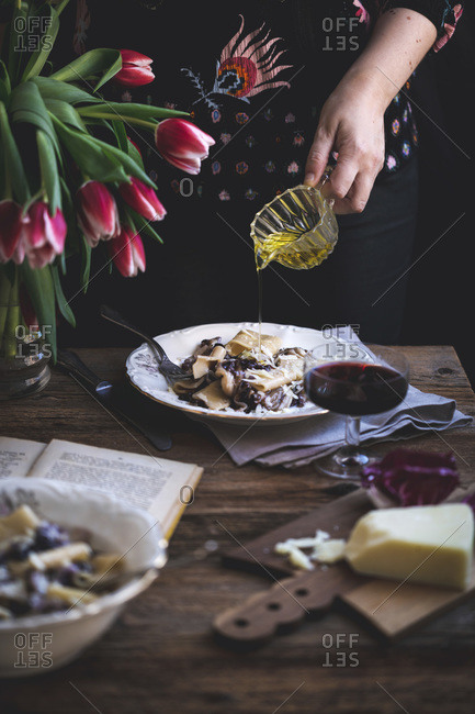 Woman drizzling olive oil over pasta with radicchio, pancetta and Parmesan