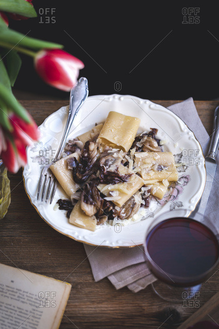 Pasta with radicchio, pancetta and Parmesan served on a plate, on a rustic wooden table