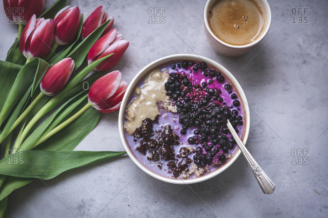 Bowl of porridge topped with melted chocolate, tahini and blueberries