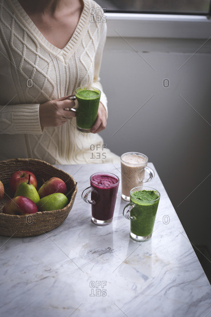 Woman sitting at the table holding a green smoothie in her hands and there are other smoothies in glasses on the table in front of her