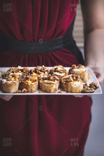 Woman holding a tray with ricotta, honey and walnuts crostini