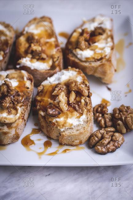 Tray with ricotta, honey and walnuts crostini
