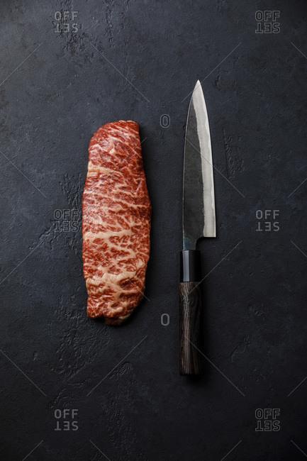 Raw fresh marbled meat Steak Wagyu beef and kitchen knife on dark background