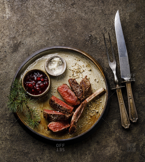 Grilled sliced Venison Ribs and berry sauce on dark background