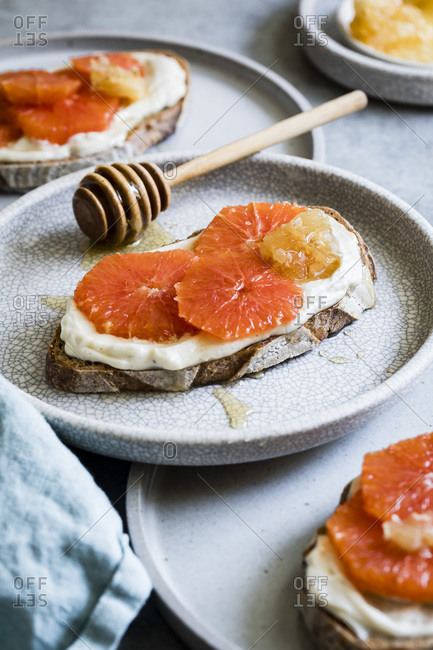 Honey orange ricotta toast on a ceramic plate. Vanilla-laced whipped ricotta gets swirled on toast and topped with orange slices and a drizzle of honey