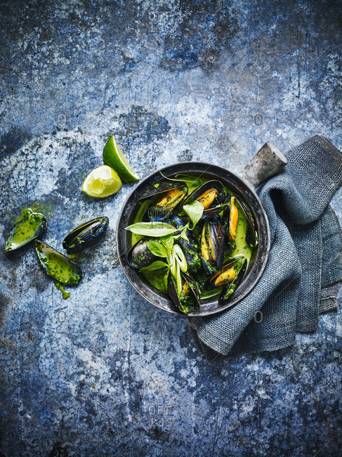 Mussels in a bowl against a blue background