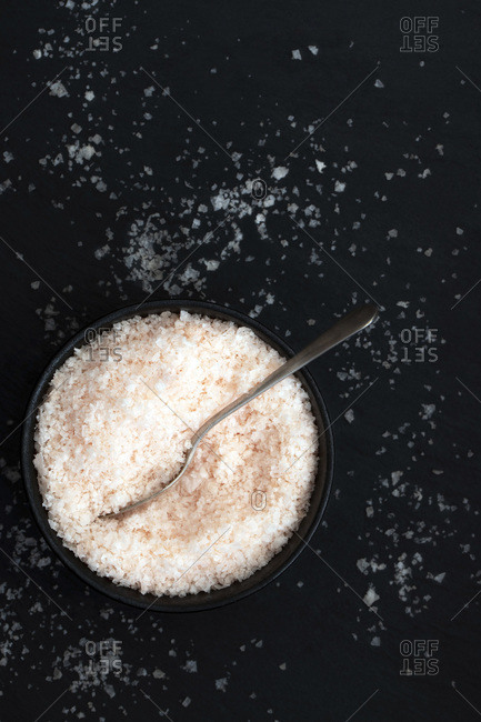 Pink salt flakes in a bowl and scattered on a black background.