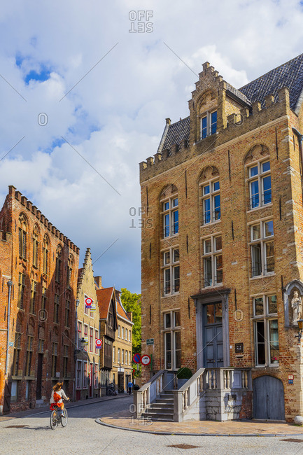 October 10, 2019: A woman riding a bike on a sunny summer day in Bruges, Belgium