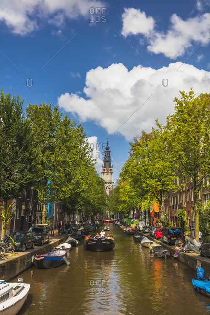 November 20, 2019: A boat with tourists with Zuiderkerk church reflecting in the water canal in Amsterdam, Holland/Netherlands