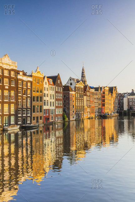 November 20, 2019: Typical houses reflecting in Damrak water canal at sunset in Amsterdam, Holland/Netherlands