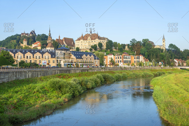 August 21, 2019: Tarnava Vare river with the old town of Sighisoara in the morning light, Unesco World Heritage Site, Transylvania, Romania