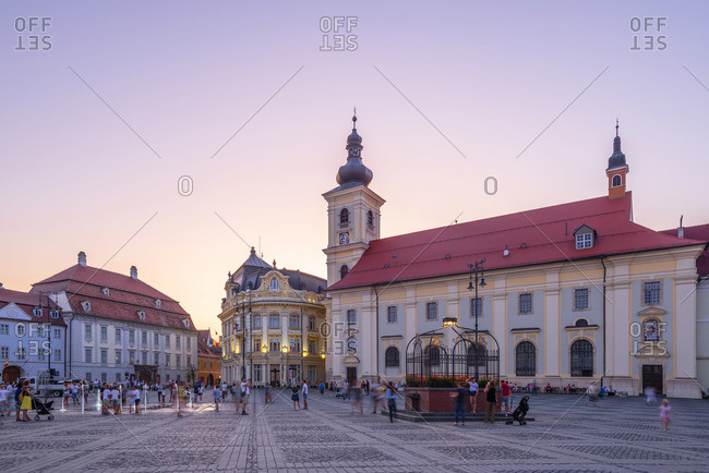 August 12, 2019: Piata Mare and the Holy Trinity Roman Catholic Church at dusk, Sibiu, Transylvania, Romania