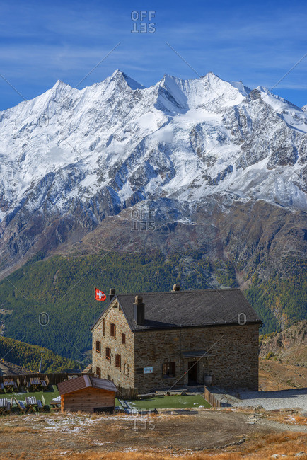October 10, 2019: View on the Weissmies mountain hut with Saas-Fee and the Mischabel mountain range, Saas-Grund, Valais, Switzerland