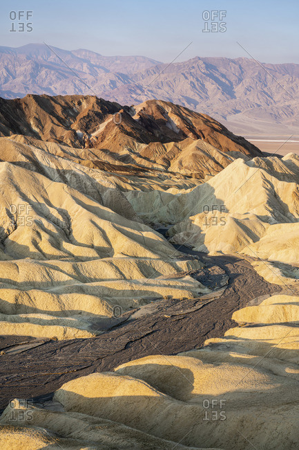 Scenic view of natural rock formations at Zabriskie Point during sunrise, Death Valley National Park, Eastern California, California, USA