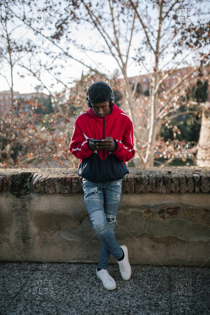 Black teenage boy listening to music on smartphone