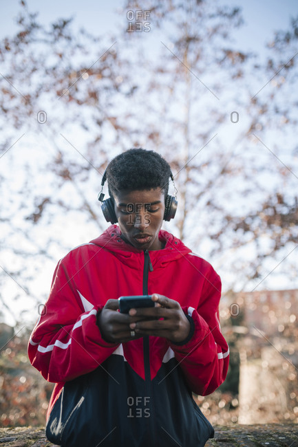 Black teenage boy listening to music with headphones on the street