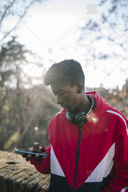 Black teenage boy using smartphone outside