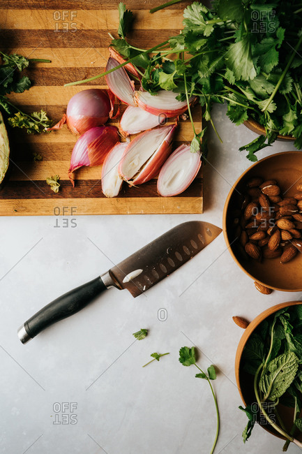 Close-up of knife, avocado, and greens on a cutting board