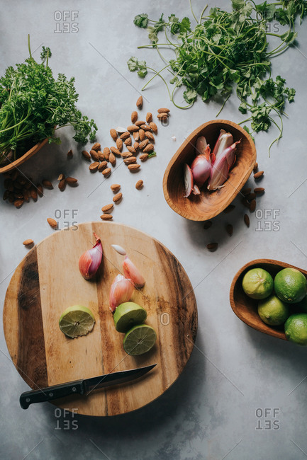Overhead view of greens and ingredients on wooden cutting board and bowls
