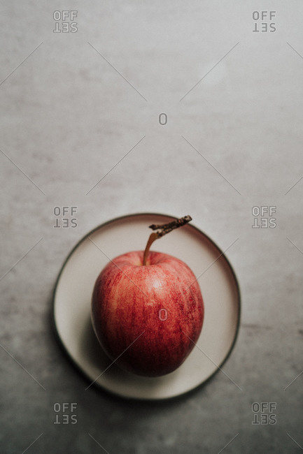 Overhead view of freshly washed apple on white plate