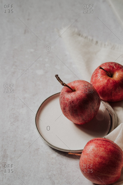 Three freshly washed apples on small white plate