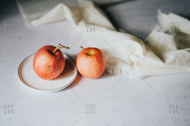 Freshly washed apples on small white plate
