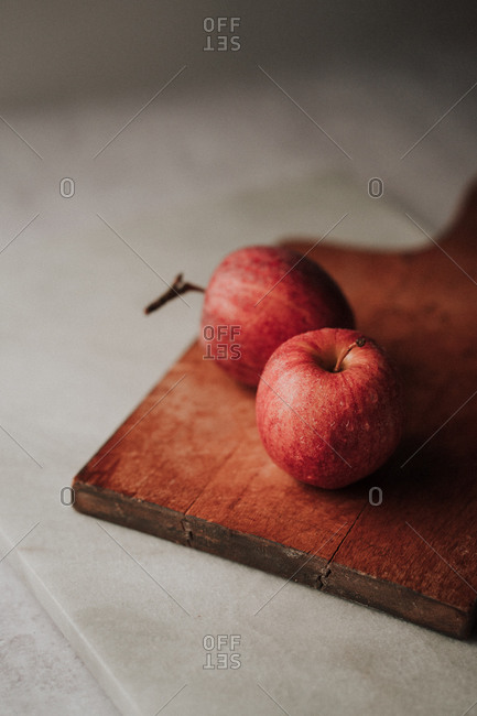 Two freshly washed apples on a cutting board
