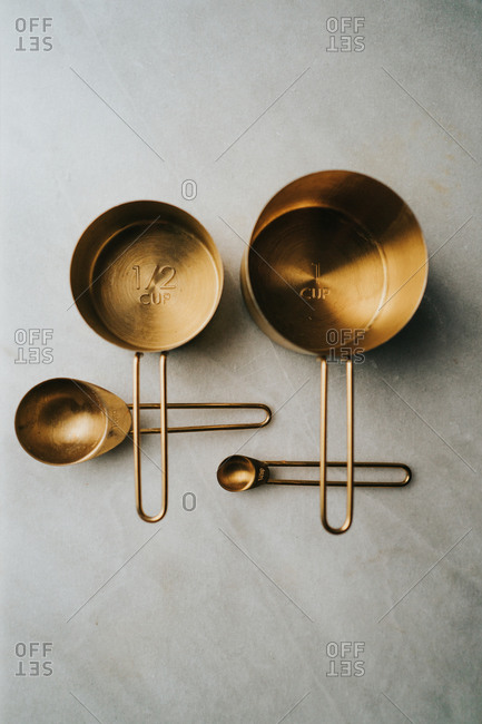 Four gold measuring cups on kitchen counter