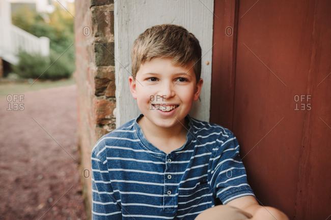 Portrait of a Smiling blonde boy wearing a blue striped shirt