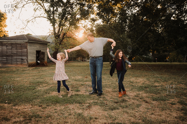 Father dancing with daughters outdoors at sunset